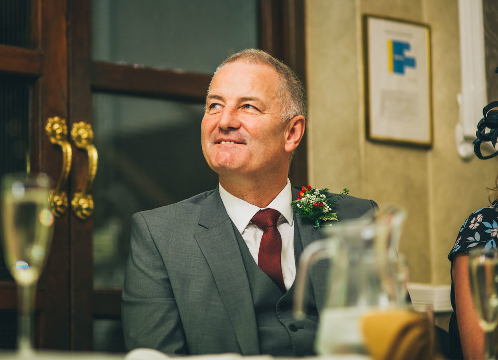 Father of the groom smiling during the wedding speech. Creative wedding photographer.