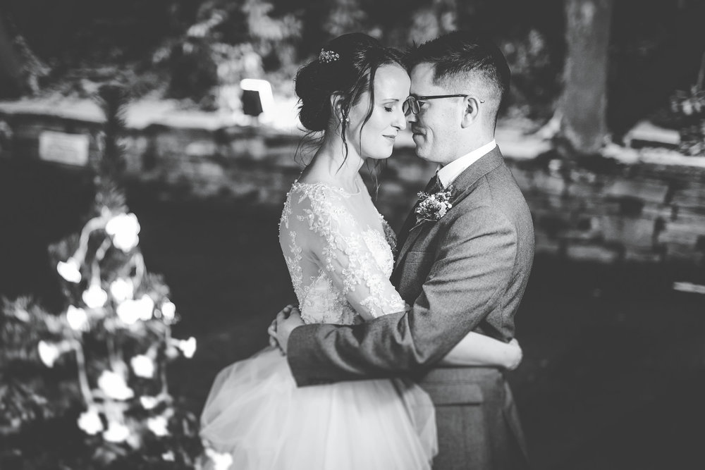 Black and white photo of the bride and groom outside. Snowy wedding photography.