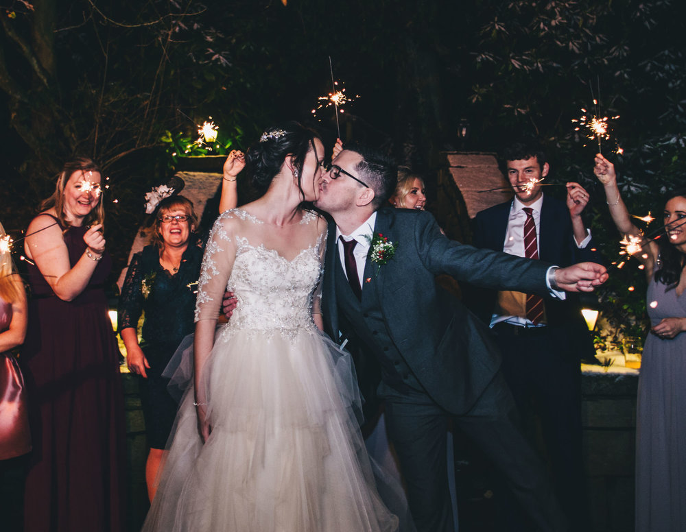 The bride and groom kissing with sparklers around them. Snowy wedding photos for a winter wedding.
