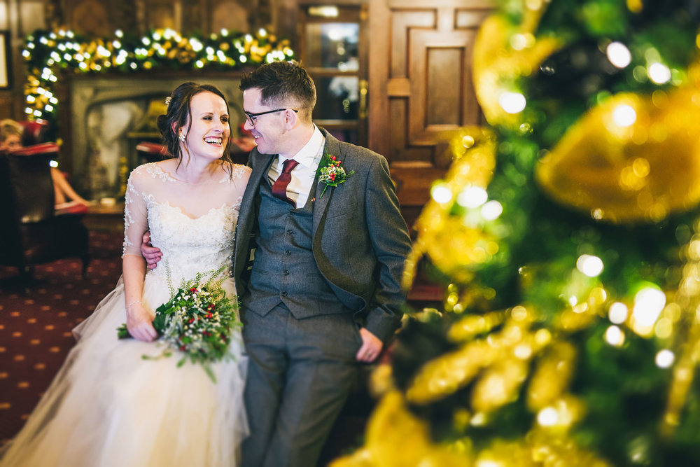 The bride and groom sat with the golden Christmas tree. Winter wedding in Lancashire.