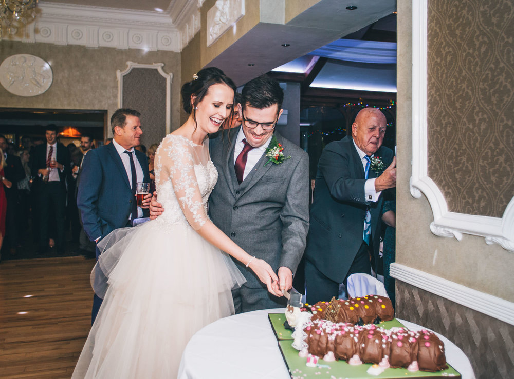 The bride and groom cutting the Colin the caterpillar cake.