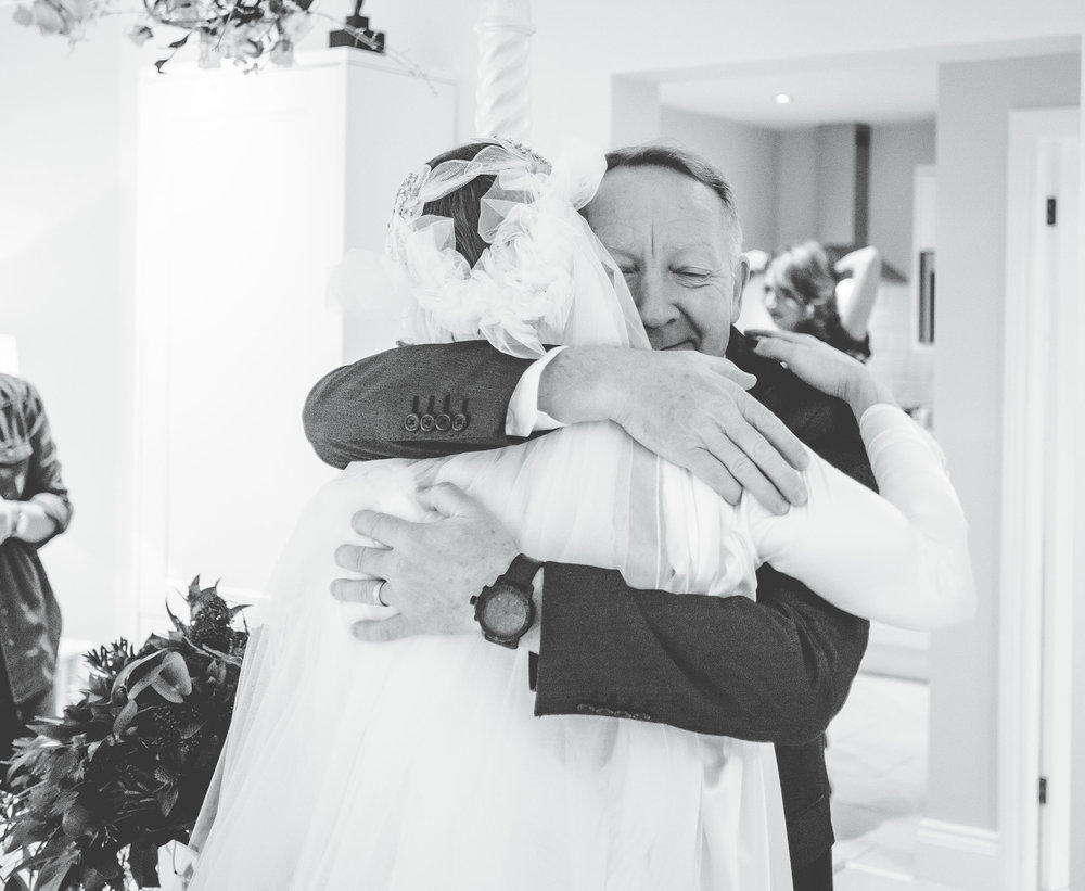 Black and white photo of the bride and her father hugging. Creative wedding photographer.