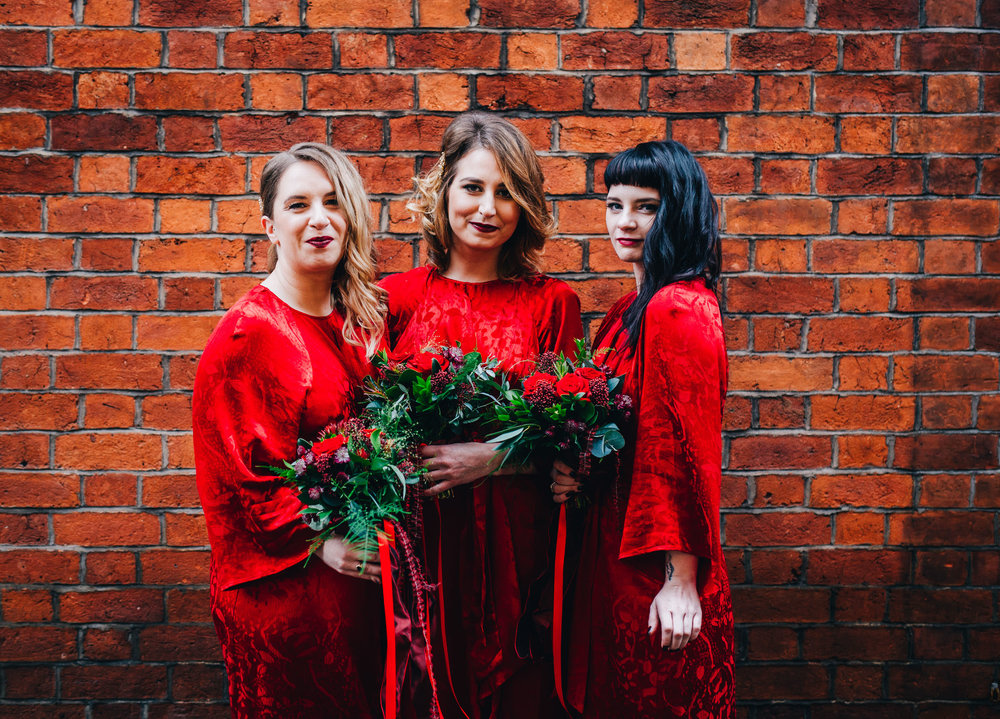 The bridesmaids in red dresses. Winter wedding in Preston.