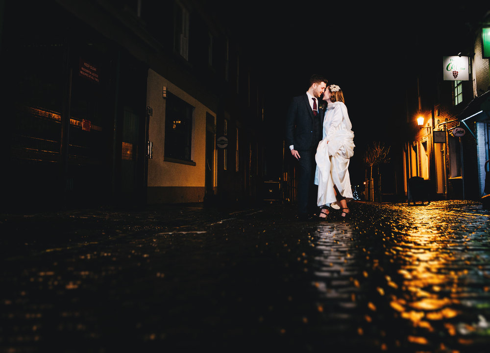 The bride and groom on the cobbles of Preston. Alternative winter wedding.