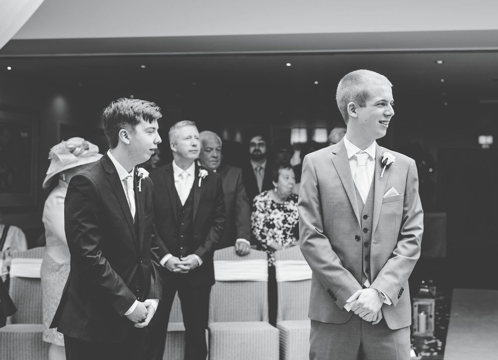 Black and white photo of the groom waiting for his bride at the alter. Creative photography.