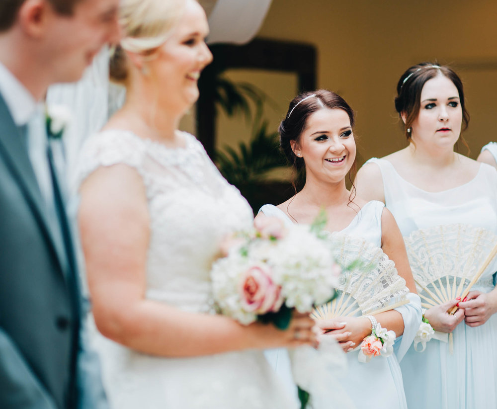 The bride at the alter, bridesmaids by her side. Lancashire wedding photographer at Mitton Hall.
