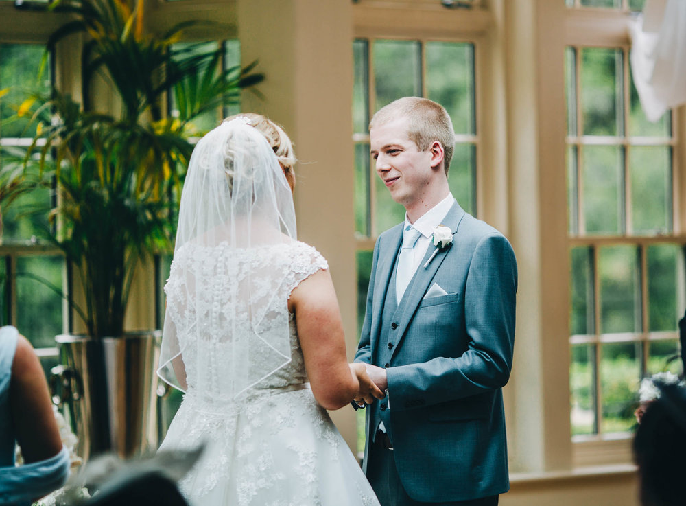 The bride and groom at the later saying their vows. Summer wedding at Mitton Hall.