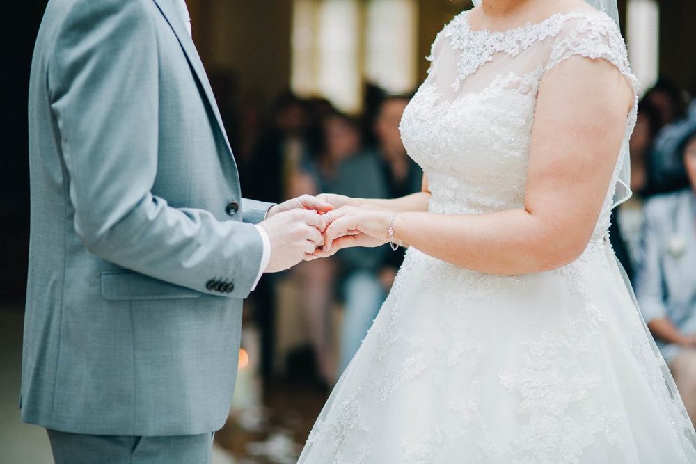 The bride and groom holding hands during the ceremony. Documentary styled wedding photographer in Lancashire.
