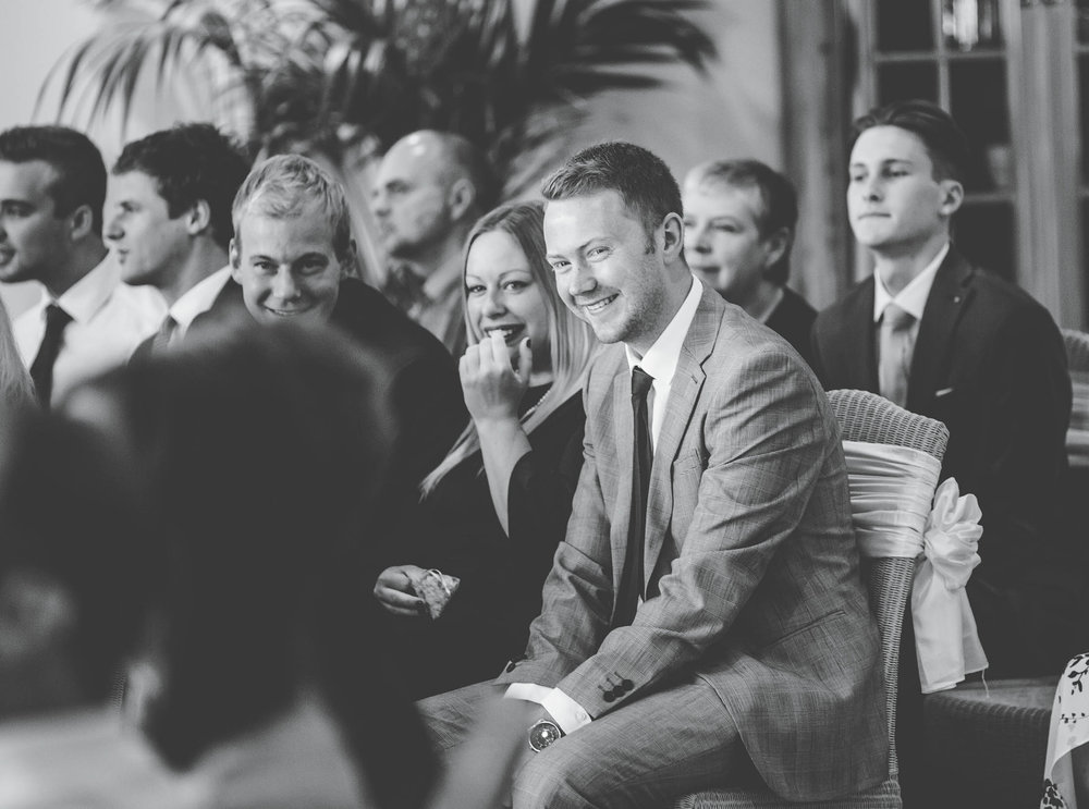 Black and white photo of the wedding guests smiling. Creative wedding photography.