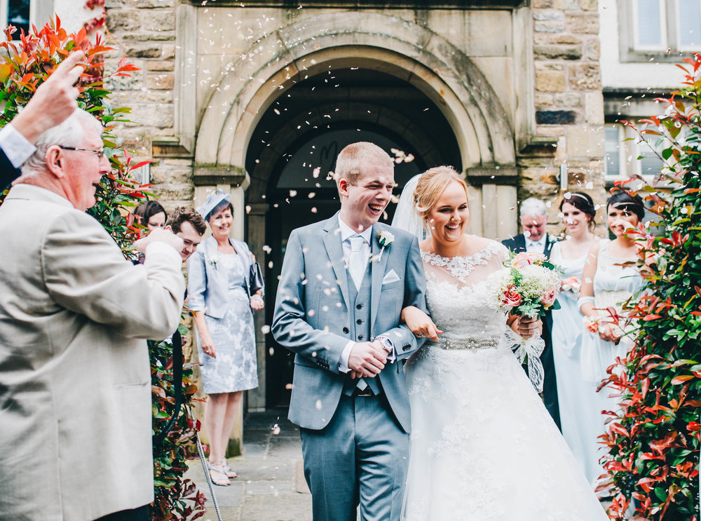 A walk through confetti for the bride and groom. Lancashire wedding photography.