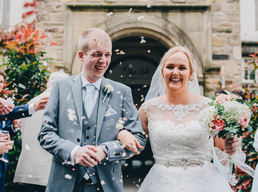 The bride and groom covered with confetti. Summer wedding at Mitton Hall.