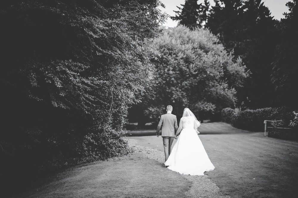 Black and white photo of the bride and groom walking. Creative wedding photography.