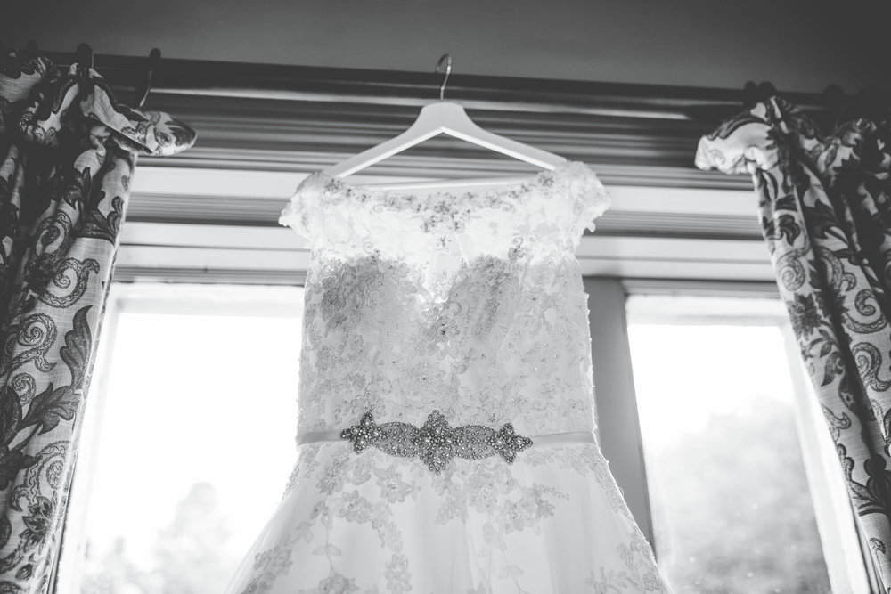 Black and white photo of the brides lace wedding dress hung up. Documentary wedding photogrpaher.