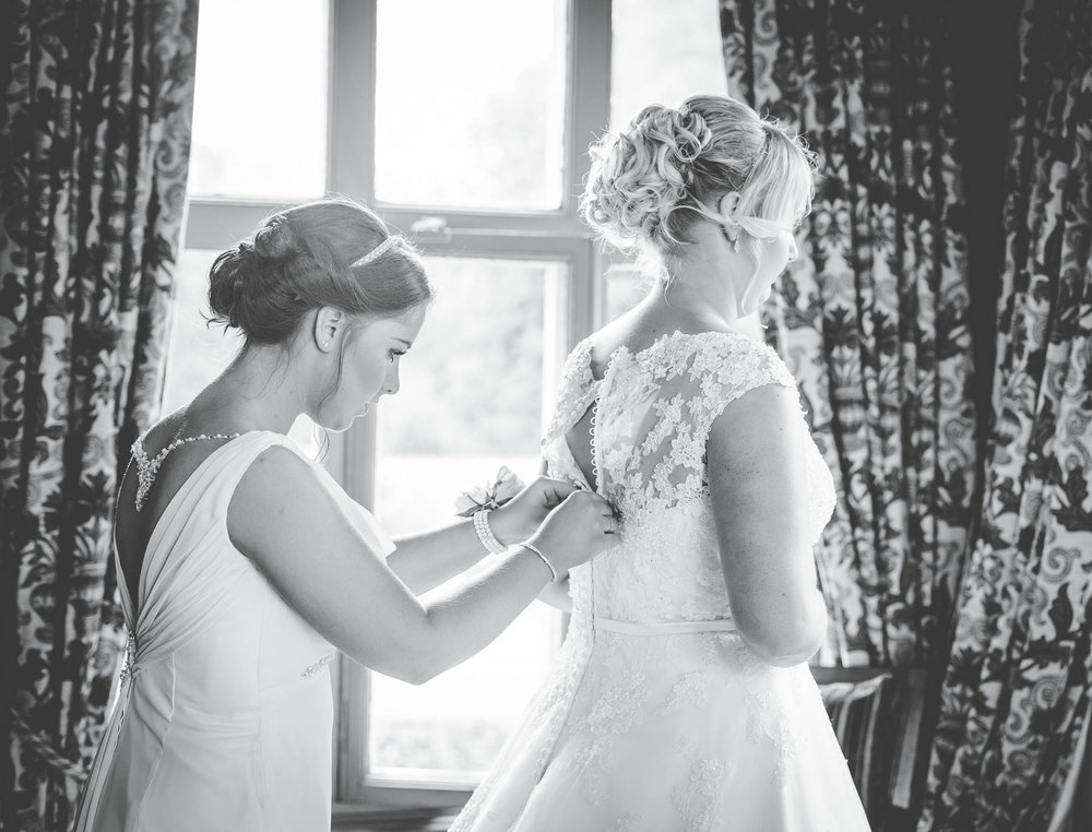 The bride having her dress buttoned. Creative wedding photography.