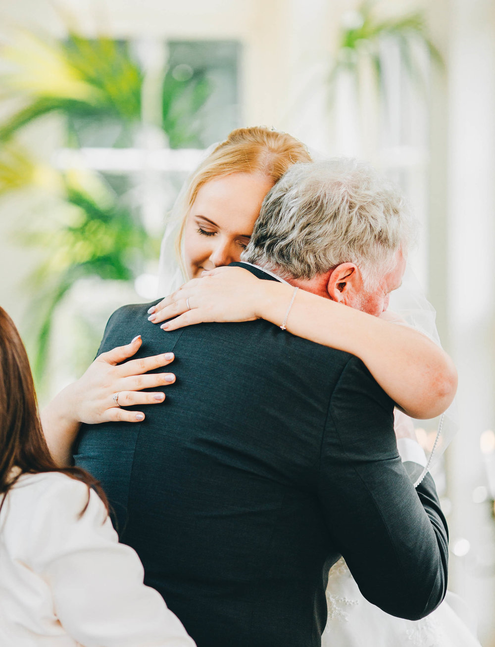 Hugs from the bride and her father. Documentary wedding photographer. Relaxed wedding.