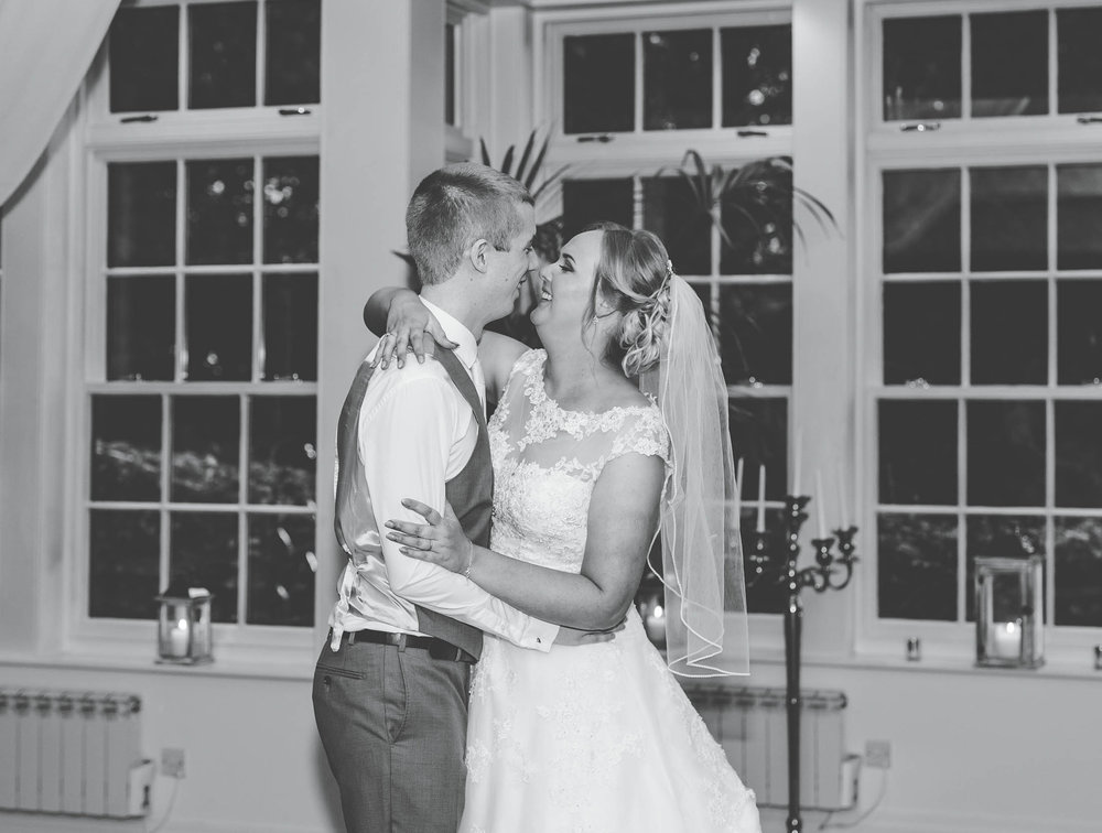 Black and white photo of the bride and groom kissing. Lancashire wedding photographer at Mitton Hall.