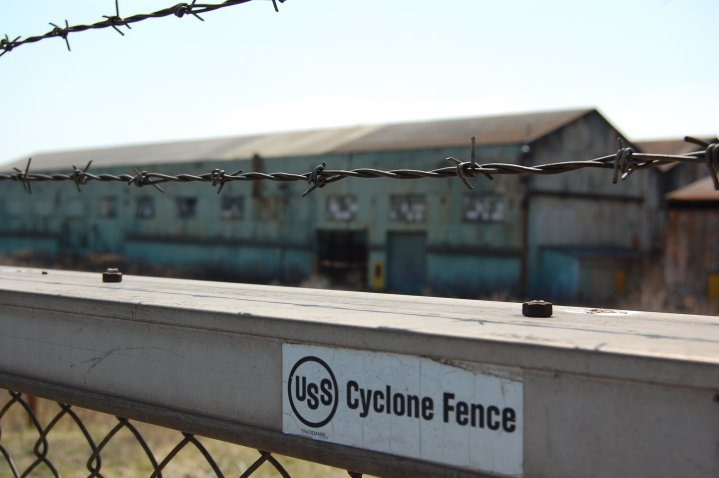 Barbed wire fence, manufactured by US Steel, surrounding shuttered steel mill. Girard Ohio.