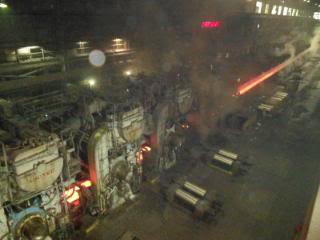 """Hot strip coming out of #6 finish mill heading to the Coiler. Notice the pollution that I breathed for 23 years."""