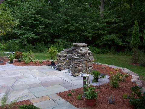 Stone retaining wall for raised planting bed, custom fireplace and patio
