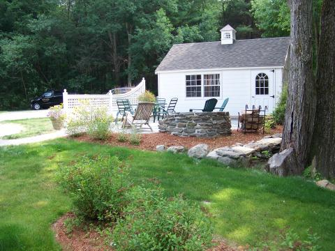 Stone retaining wall with custom fireplace, patio and custom fence