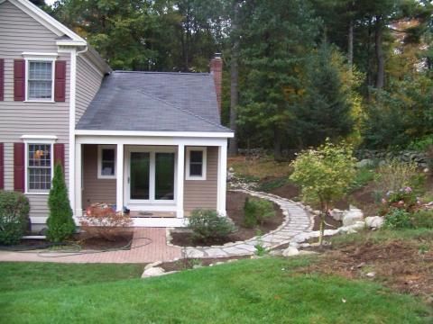 Custom addition with open porch, site stone walls and stone steps, plantings