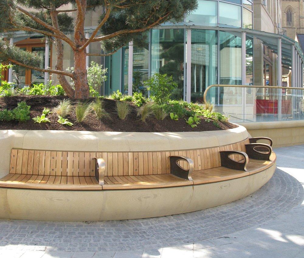 Tudor Square - planter bench    Bespoke bronze arm rest integrated bench in planter.