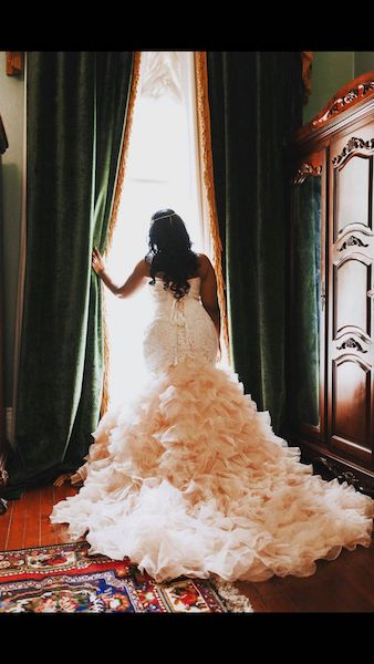 Bride in an Allure Dress Looking out a window