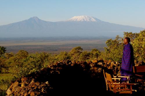 Maasai overlooking mount Kilimanjaro from Tembo House, Campi ya Kanzi, Kenya