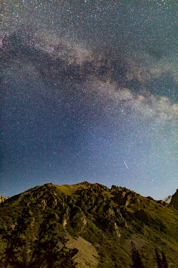 Looking due East, a satellite makes a bright streak over the hills; shooting stars do not have such continuous patterns. The moon makes the light from the right of the photo, dimly lighting the mountains.