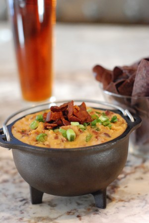 This Ale, Bacon and Cheddar dip was inspired by my mother's home state of Wisconsin, and the football team that I love. It's perfect for entertaining on any given Sunday with family or friends. The dip is best served hot, and I recommend using a fondue pot or small cast iron caldron. Lodge makes the little cast iron caldron I used in the picture above. I love it because it stays hot for a long time without a heating element, which is perfect when children are around. The company was founded in Tennessee over 100 years ago and they're still making the best skillets, Dutch ovens and griddles you can buy. Serve this dip with tortilla or pretzel chips.  Active Time: 30 minutes Makes about 4 cups  Ingredients  1½ lb thick cut applewood smoked bacon 2 cups sweet onion, diced 1 tablespoon garlic, diced 2 tablespoons flour 1 bottle amber ale – I like to use Boont Amber Ale from Anderson Valley Brewing Co. ½ cup whole milk 4 oz cream cheese, softened 4 oz finely shredded (about 2 ½ cups) sharp cheddar 4 oz finely shredded (about 2 ½ cups) aged extra sharp cheddar 1 scallion, light and dark green parts only, finely chopped  Preparation  Cut bacon into ¼-inch strips. Heat a large skillet over medium-high heat and cook the bacon until crispy, 4 to 6 minutes. Transfer the bacon to a paper towel lined plate. Pour off all but 2 tablespoons of the bacon fat from the skillet. Turn the heat to medium and add the onions. Sauté until onions are soft and translucent, about 5 minutes. Add the garlic and cook for another minute or two. Sprinkle the flour over the onions and cook, stirring, until flour has coated onions and is lightly golden brown, 1 to 2 minutes. Add one bottle of ale slowly, whisking as you pour to avoid lumps. Cook until mixture has thickened, 3 to 4 minutes. Add the milk, and then cream cheese, whisking until smooth after each addition. Turn the heat to low and fold in the shredded cheese, stirring until melted. Gently fold in bacon, reserving about ¼ cup for garnish. Transfer the dip to a small fondue pot or little cast iron cauldron. Top with remaining bacon and chopped scallions.  Serve with tortilla or pretzel chips.