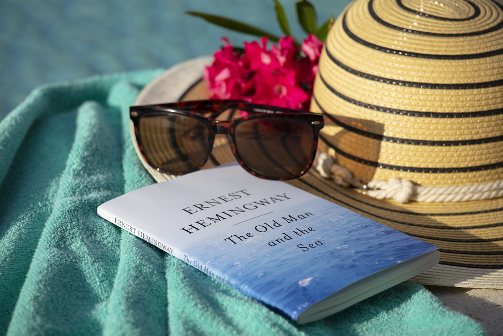 Image of sunglasses, book, and sun hat on pool towel