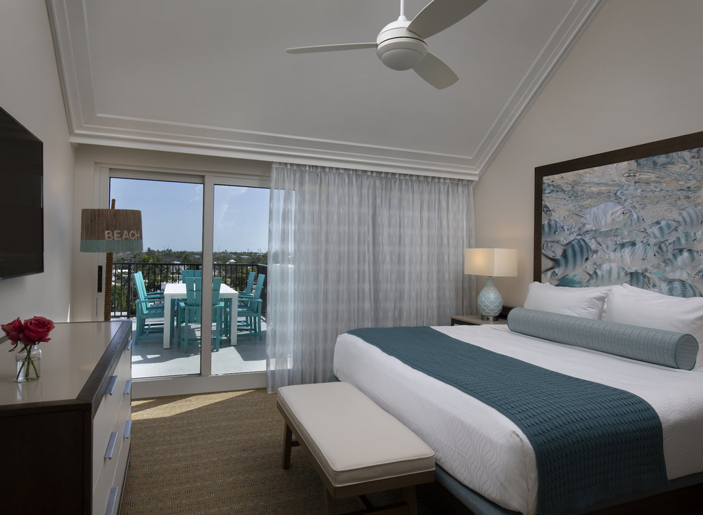 The Laureate Key West king bed guest room with balcony