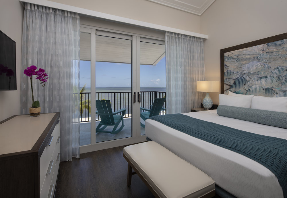 The Laureate Key West king bed guestroom with balcony ocean view