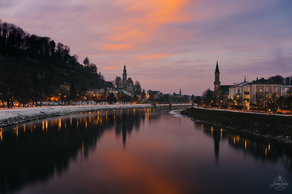 Sony a7rii | 35mm 2.8 | f11 | 8 sec | ISO 100 | Streetlights composited in to sunset photograph  The Salzach runs right through the Old Town, and there are several pedestrian only bridges that cross. This is looking NW from the Makartseg bridge.     Much thanks to my wonderful mother for hanging out in a grocery store while I was taking this photo in the cold.     This image is available for print,  click here  to visit our store.