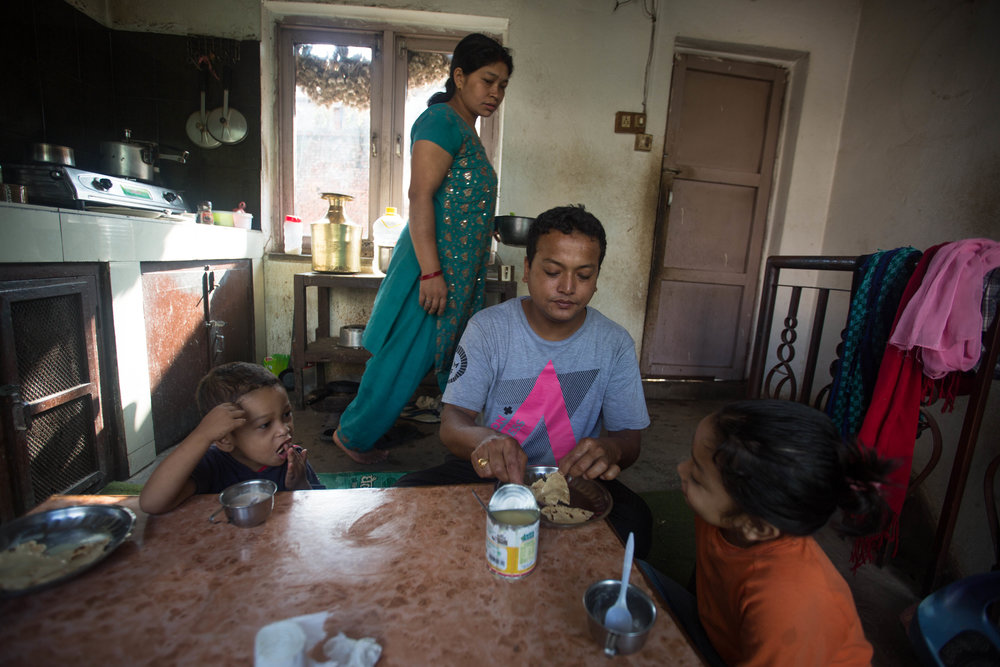 Tirtha Shakya, who prefers his birth name and male pronouns when with his family, eats a breakfast of roti and condensed milk with his wife, Uma, and two children in Kirtipur, Nepal, on Aug. 15, 2016.