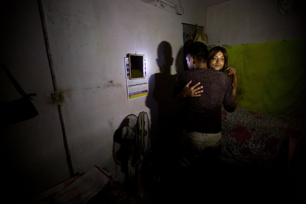 Sweety greets a client, who prefers to remain unidentified, in her room during a blackout on Aug. 16, 2016, in Kathmandu, Nepal.