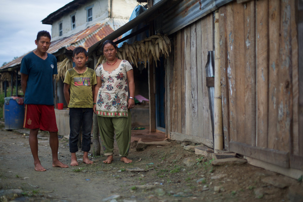 Bhoj, Sunil and Chari stand for a portrait outside their home in Gorkha, Nepal, on Aug. 1, 2016.