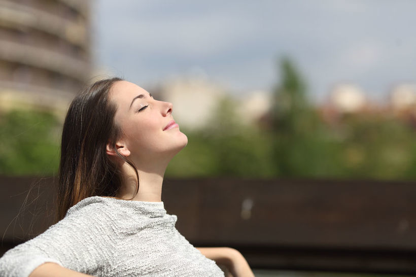 44652546 - urban woman sitting on a bench of a park and breathing deep fresh air