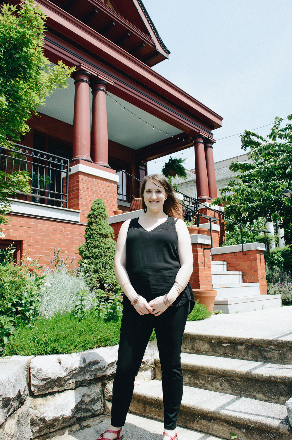 Lila standing in front of the home where her puppet troupe performs