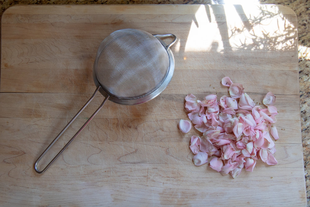 Straining out the rose petals (which didn't work as I had hoped)