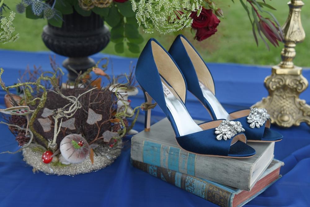 Floral arrangement by La Tulipe.Mushroom crown and vintage books by Relics Vintage Rentals.Jeannie Crystal Trim open toe shoe by Badgley Mischka.