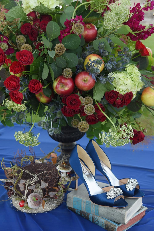 Floral arrangement by La Tulipe. Mushroom crown and vintage books by Relics Vintage Rentals.Jeannie Crystal Trim open toe shoe by Badgley Mischka.