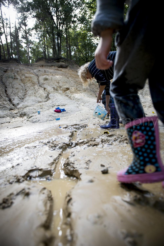 Oma met kleinkinderen aan het spelen in het bos, in de modder. Daily life familiereportage. Ongedwongen familie documentaire. Ellis Peeters photography