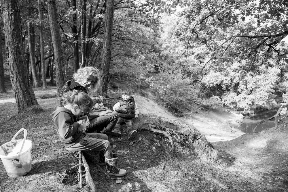 Oma is met haar kleinkinderen aan het picknicken in het bos. Zwart wit daily life familie reportage. Documentaire fotografie door Ellis Peeters Photography.