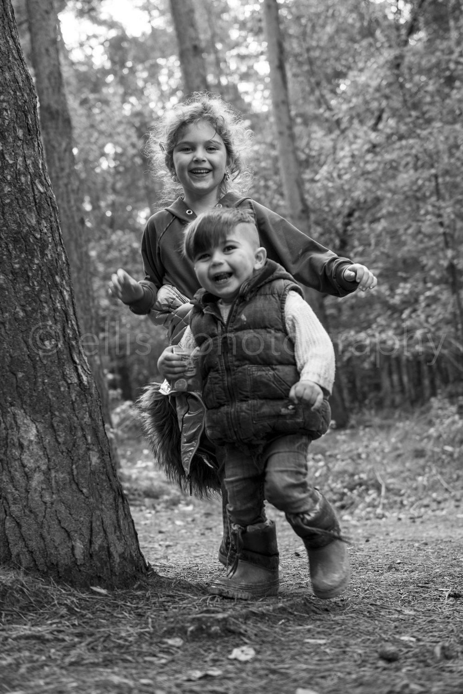Broer en zus rennen vrolijk en blij om een boom. Daily life familie documentaire / reportage. Ongedwongen foto's in de natuur, in het bos. Ellis Photography