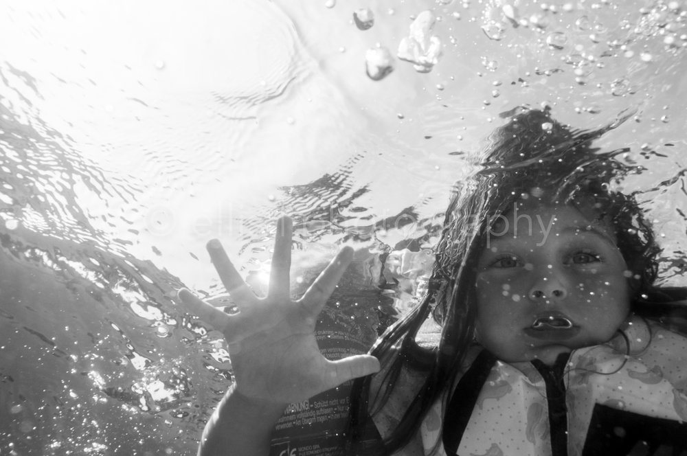 Girl swimming in a pool. Daily life Underwater photography. Photo taken from underneath the girl. Onderwater fotografie. Jong meisje zwemt in het water. Relaxed. Ellis Photography