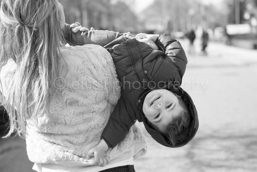 Kind word opgetild en kijkt ondersteboven achterom. Spontane familie documentaire. Daily life familiereportage gemaakt door Ellis Peeters photography.