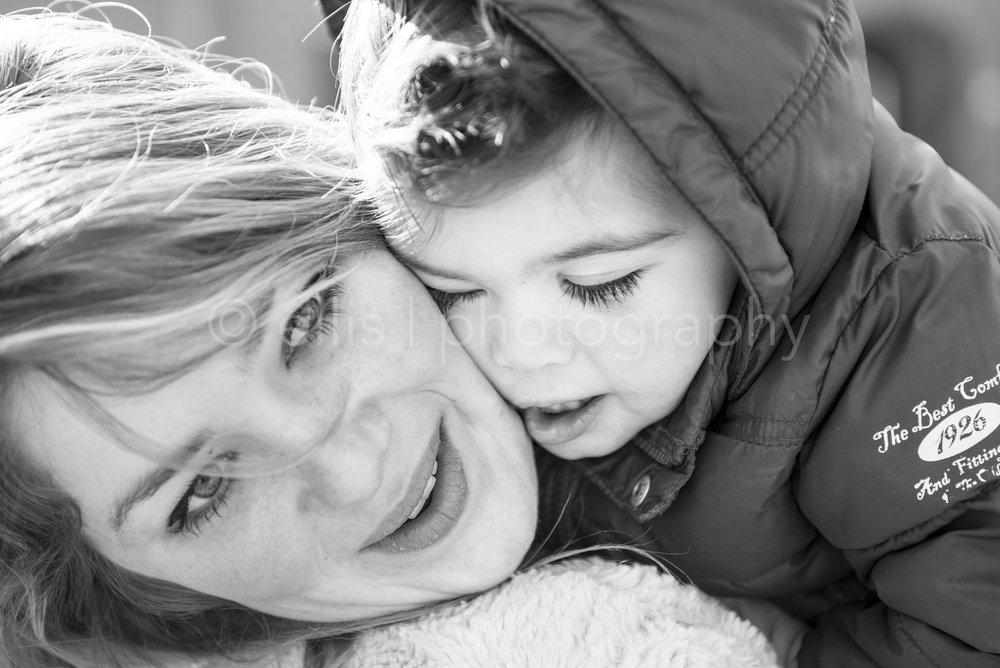 Zwart wit portret van een volwassene met haar neefje. Spontane daily life fotografie buiten in de natuur. Ellis Photography fotografeert families in hun dagelijks leven. Documentaire fotografie.
