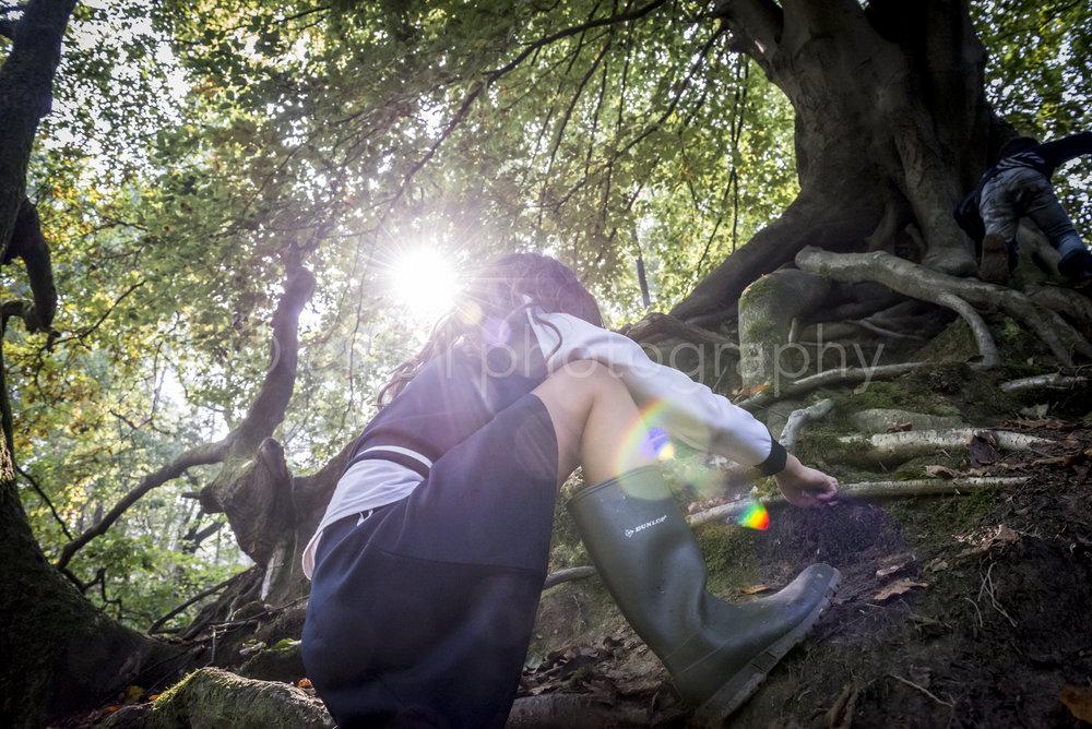 Kids are on adventure in the woods, girl wearing Dunlop boots. Daily life photography. Sun shines through the trees. Kinderen zijn op avontuur in het bos. Zon schijnt door de bomen. Meisje draagt Dunlop laarzen.