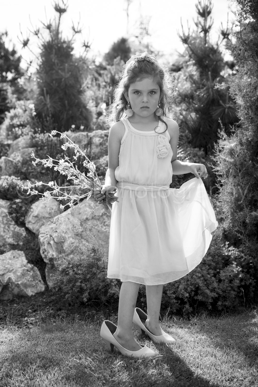 Beautiful young girl dressed in a pretty dress with too big heels, holding flower. Daily life Black and white photography by Ellis Peeters. Jong meisje met een mooie jury aan en te grote hakken schoenen. Daily life photography. Meisje houdt bloemen vast.